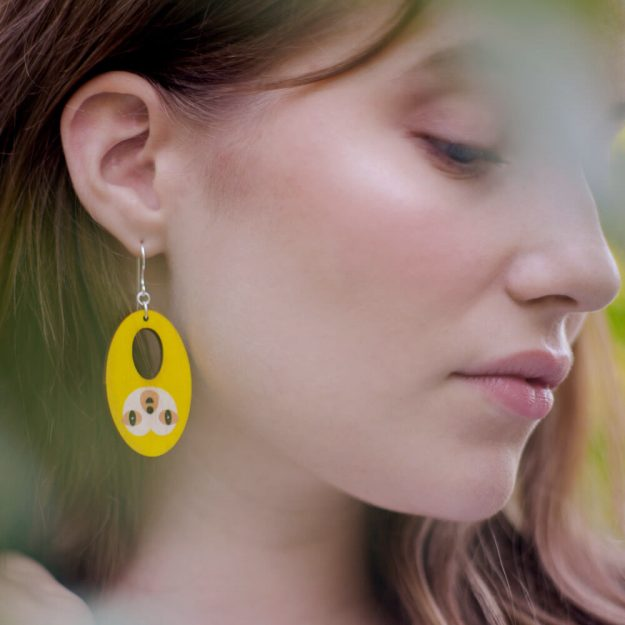Woman wearing wooden sloth earrings in yellow